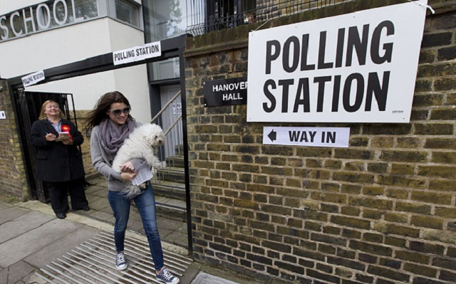 A woman carrying a dog leaves a polling